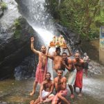 Padayatris stand in front of a waterfall with Gaura Nitai